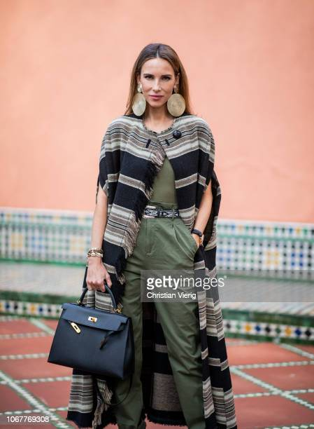 Alexandra Lapp is seen wearing a long Huan fringed striped wool cape from Isabel Marant utility trousers in khaki green by HM black leather belt with...