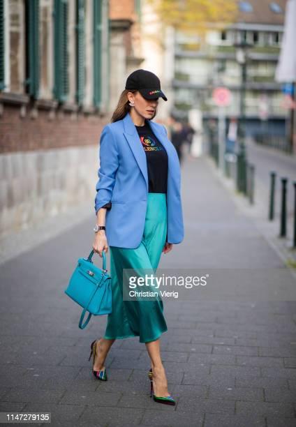 Alexandra Lapp is seen wearing a long turquoise satin skirt from Zara, a black logo print t-shirt from Balenciaga, blue oversized blazer from Zara,...