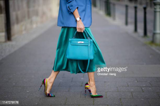 Alexandra Lapp is seen wearing a long turquoise satin skirt from Zara, blue oversized blazer from Zara, the So Kate stripy glitter multicolored suede...