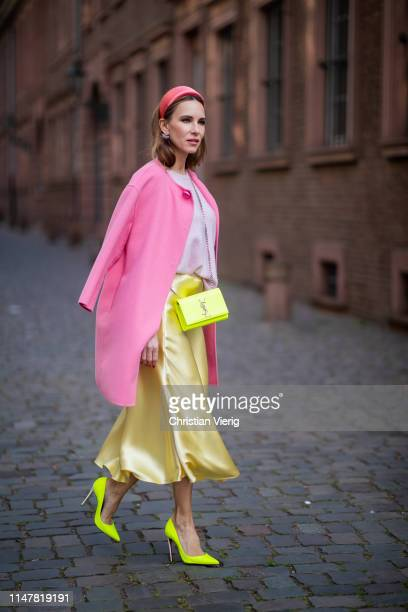 Alexandra Lapp is seen wearing a long yellow flared satin skirt from Zara, light pink round neck cashmere pullover by Jadicted, a classic pink...