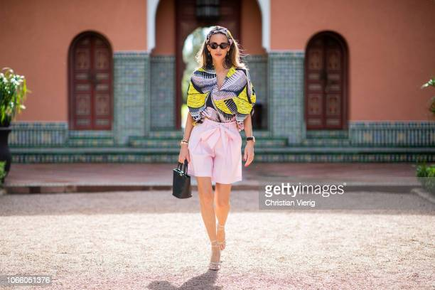 Alexandra Lapp is seen wearing a loose tunic blouse in a pink yellow and black pattern with wide arms with a matching silk printed scarf and a light...