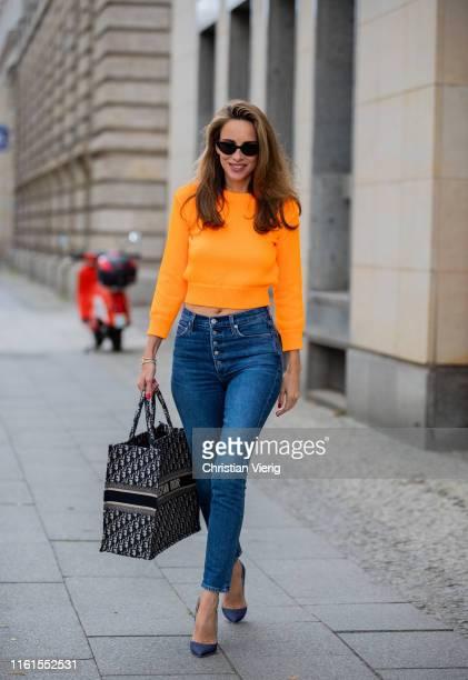 Alexandra Lapp is seen wearing a neon orange cropped sweater from Les Rêveries, Adriano Goldschmied ex-boyfriend jeans, Christian Louboutin So Kate...