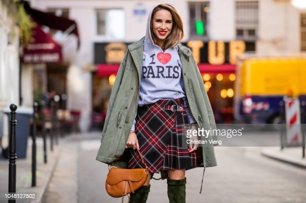 Alexandra Lapp is seen wearing a plaid kilt skirt from maje an I love Paris sweatshirt from a souvenir shop in Paris a green parka jacket with teddy...