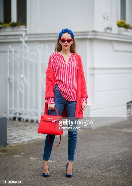 Alexandra Lapp is seen wearing a red chunky knit cardigan styled over a red-white-striped blouse and blue jeans - all from Brax, red cat-eye...