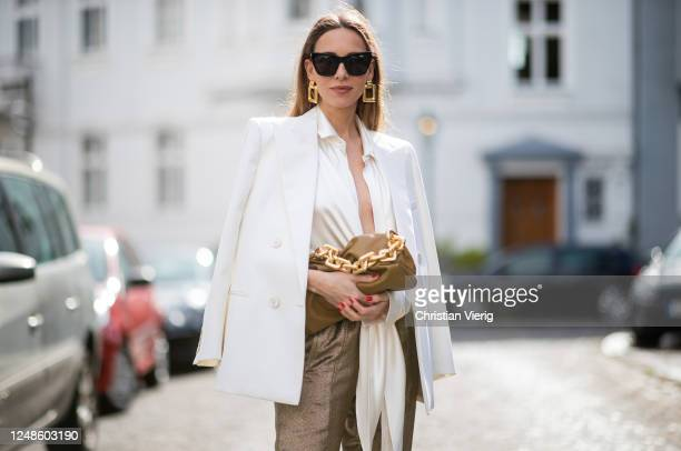 Alexandra Lapp is seen wearing a Saint Laurent tie front silk satin blouse in white Lurex track pants from Saint Laurent in gold doublebreasted wool...