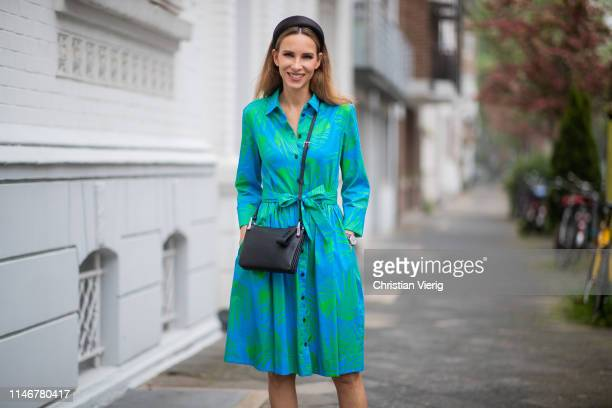 Alexandra Lapp is seen wearing a swinging blue shirtdress with a palm tree print, a black leather handbag - all from Marc Cain and a silk satin...