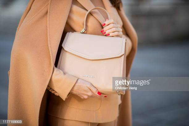 Alexandra Lapp is seen wearing a toffee colored total look from Marc Cain with belted blazer and wool-cashmere coat, bag during Paris Fashion Week...