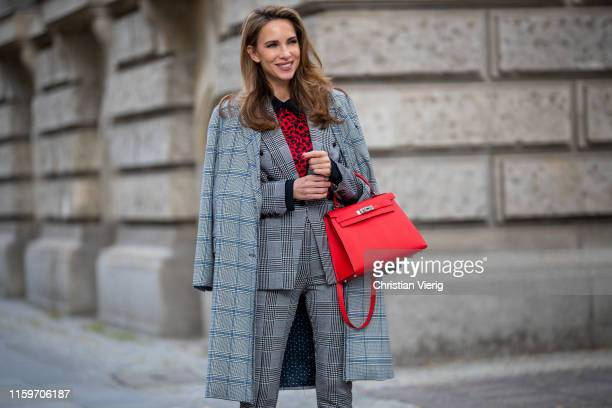 Alexandra Lapp is seen wearing a total look by Steffen Schraut with grey checkered coat, grey checkered suit and red leopard blouse,red Hermès Kelly...
