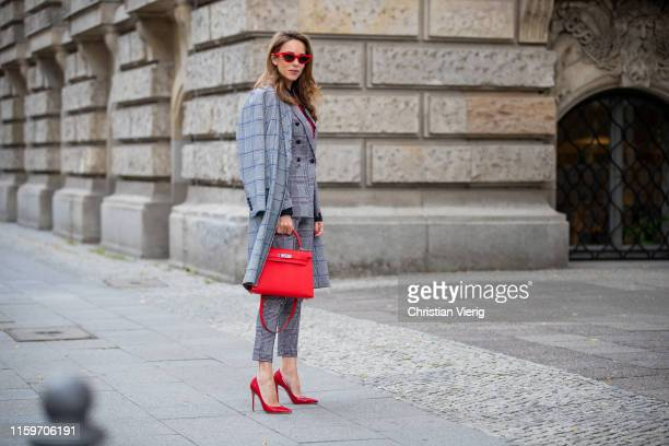 Alexandra Lapp is seen wearing a total look by Steffen Schraut with grey checkered coat grey checkered suit and red leopard blouse red Céline cat eye...