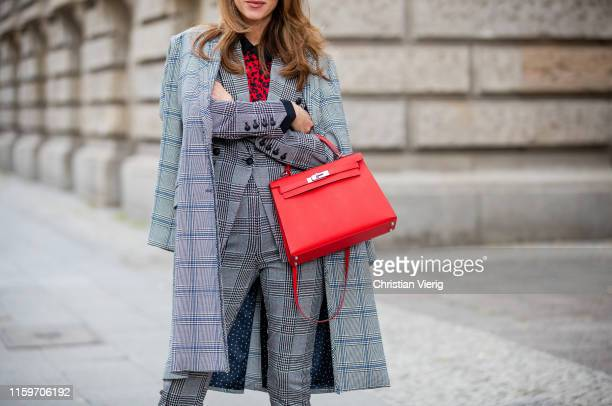 Alexandra Lapp is seen wearing a total look by Steffen Schraut with grey checkered coat, grey checkered suit and red leopard blouse, red Hermès Kelly...