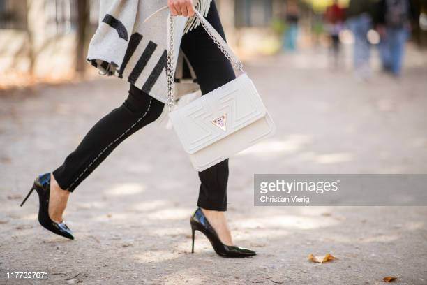 Alexandra Lapp is seen wearing a total look from Marc Cain with a grey woolen jacket like a blanket with black padded sleeves, white Marc Cain bag,...