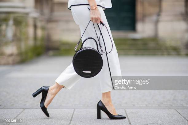 Alexandra Lapp is seen wearing a white and black suit, round shoulder-bag in black with croco print, black pumps all from Marc Cain during Paris...
