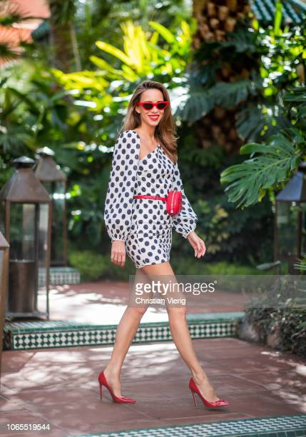 Alexandra Lapp is seen wearing a white mini dress with Polka dots and one asymmetric shoulder from Lovers FRIENDS from Rebelle a red waist belt bag...