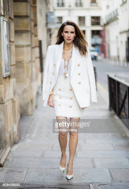 Alexandra Lapp is seen wearing a white tweed blazer with golden buttons and a matching tweed mini skirt with golden buttons from Balmain a white silk...