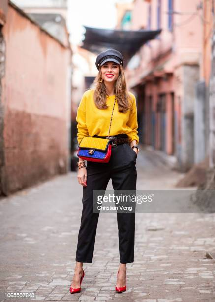 Alexandra Lapp is seen wearing a yellow crewneck cashmere sweater from Jardin des Orangers highwaisted trousers in dark grey by HM Graphic Flap Bag...