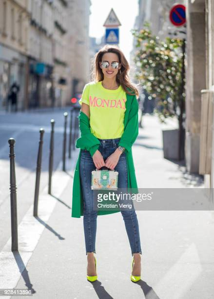 Alexandra Lapp is seen wearing a yellow neon tshirt with pink letters writing Monday by Alberta Ferretti a blue pair of AG Jeans a green coat from...