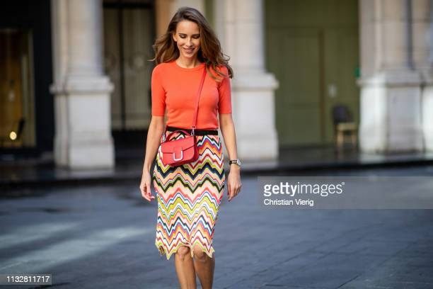 Alexandra Lapp is seen wearing an apricot colored Marc Cain coral knitted top and multicolored knitted skirt paired with two tone sling pumps and and...