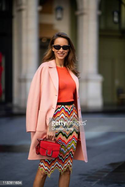 Alexandra Lapp is seen wearing an apricot colored Marc Cain wool coat coral knitted top and multicolored knitted skirt and and a red leather mini bag...