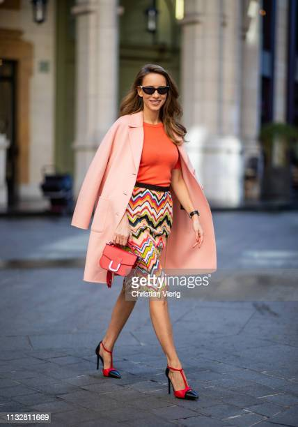 Alexandra Lapp is seen wearing an apricot colored Marc Cain wool coat coral knitted top and multicolored knitted skirt paired with two tone sling...