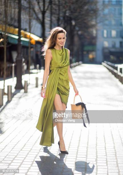 Alexandra Lapp is seen wearing an asymmetric layered silk dress from Offwhite in green with a basket bag from Sensistudio with a black bow and black...