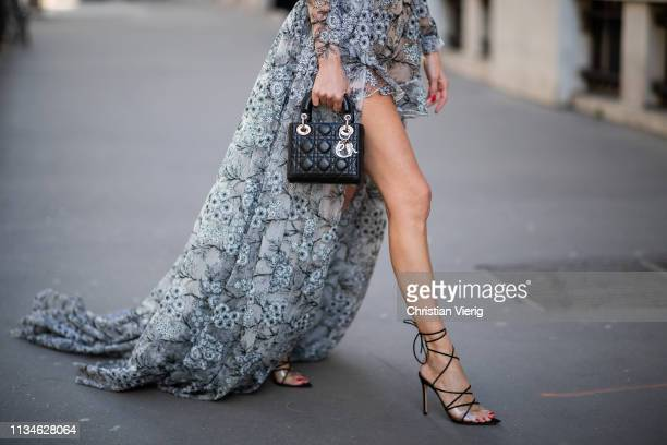 Alexandra Lapp is seen wearing an evening gown/ jumpsuit combination with embroidered flowers by Lana Mueller X Alexandra Lapp with a black leather...