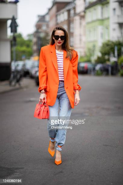 Alexandra Lapp is seen wearing an orange oversized-blazer from The Attico, striped T-shirt with shoulder pads from Mango, Levis 501 Jeans in light...