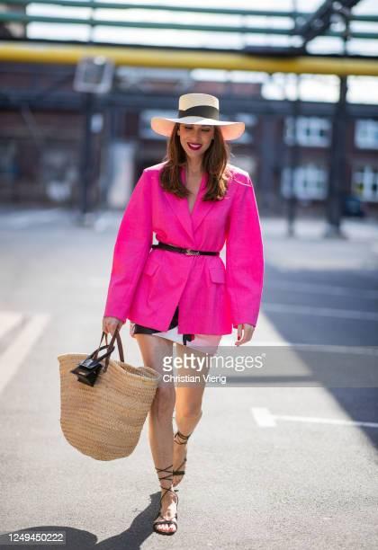 Alexandra Lapp is seen wearing an oversized blazer in pink from H&M, Gucci waist belt, Sensi Studio straw hat, Sensi Studio straw bag in combination...