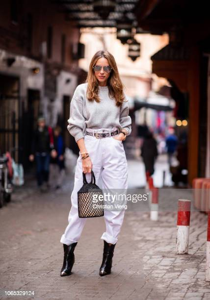Alexandra Lapp is seen wearing an oversized grey wool sweater from HM white highrise boyfriend style jeans from Isabel Marant Etoile a black leather...
