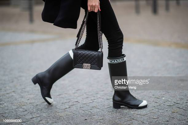 Alexandra Lapp is seen wearing black skinny pants with golden buttons by Veronica Beard and Chanel rain boots, the Chanel Le boy bag during the...
