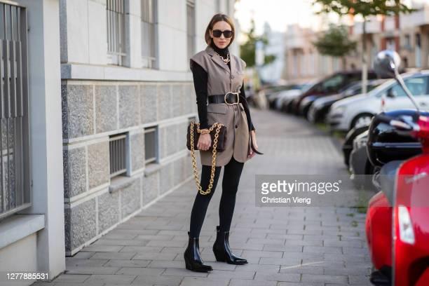 Alexandra Lapp is seen wearing Bottega Veneta square-frame acetate and gold-tone sunglasses, Bottega Veneta The Chain Cassette suede shoulder bag in...