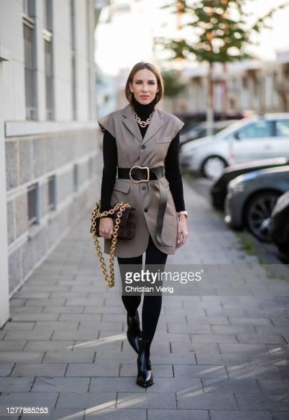 Alexandra Lapp is seen wearing Bottega Veneta The Chain Cassette suede shoulder bag in chocolate-brown, Loulou blazer minidress in brown from Frankie...
