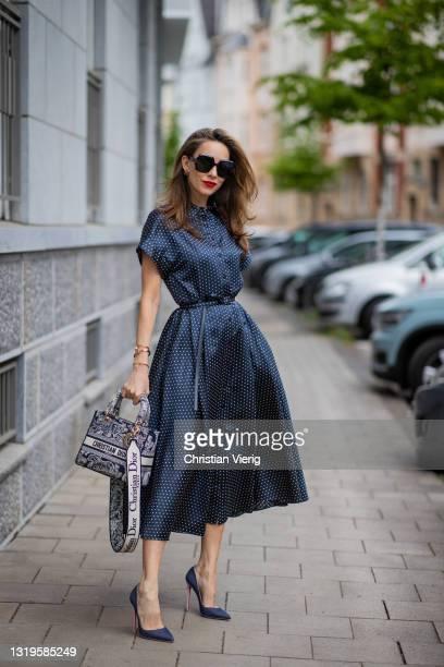 Alexandra Lapp is seen wearing CHRISTIAN DIOR silken Shirt Dress in navy, CHRISTIAN DIOR reverse embroidery medium Lady D-Lite blue toile de jouy and...