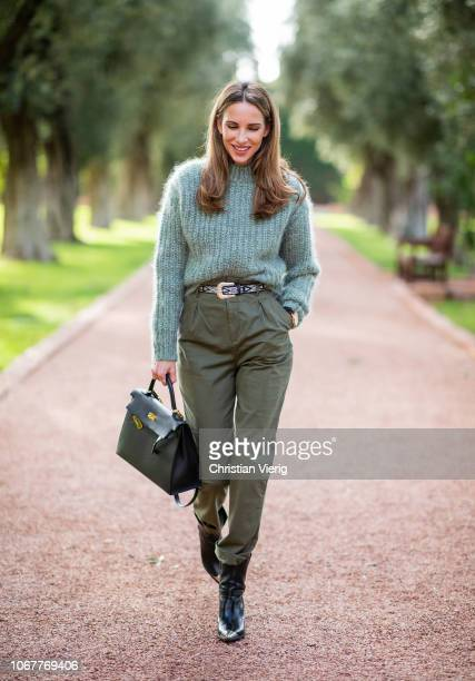 Alexandra Lapp is seen wearing chunkyknit wool jumper by HM in dusky green utility trousers in khaki green by HM black leather belt with white...