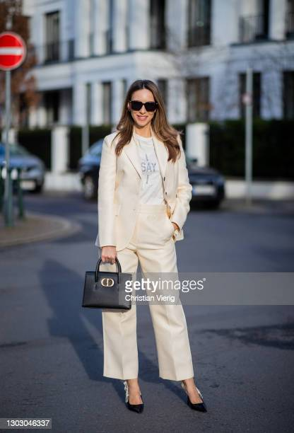 Alexandra Lapp is seen wearing Cruise 2021 CHRISTIAN DIOR blazer in creme, CHRISTIAN DIOR trousers in creme, CHRISTIAN DIOR I say I t-shirt,...