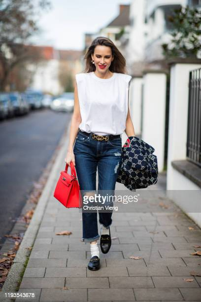 Alexandra Lapp is seen wearing dark denim blue jeans AG Jeans white sleeveless muscle tshirt with padded shoulders The Frankie Shop Gucci GG horsebit...