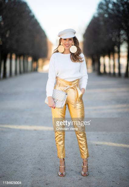 Alexandra Lapp is seen wearing gold leather high waist paperbag pants from Pearl and Rubies white knit pullover from Ouí a white Baker Boy hat from...