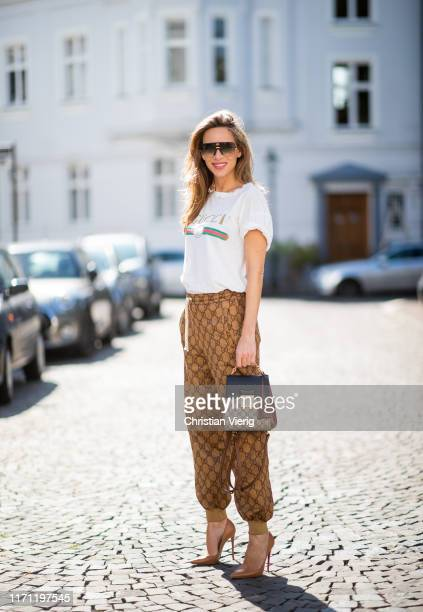 Alexandra Lapp is seen wearing Gucci GG jogging pants, brown Christian Louboutin So Kate pumps, sand colored Parenti's sweater, white Gucci logo...