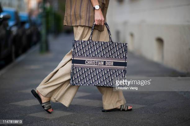 Alexandra Lapp is seen wearing high waisted wide leg pants from Staud, Dior Dway mules, Dior Book Tote Dior Oblique bag and a Dior foulard on a blue...
