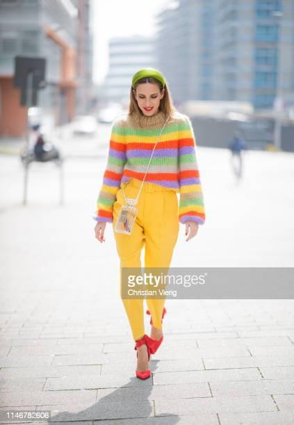 Alexandra Lapp is seen wearing highwaist yellow pants from Zara multicolored hand knit sweater from Ganni green silk satin hairband from Prada red...