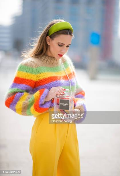 Alexandra Lapp is seen wearing highwaist yellow pants from Zara multicolored hand knit sweater from Ganni green silk satin hairband from Prada and...