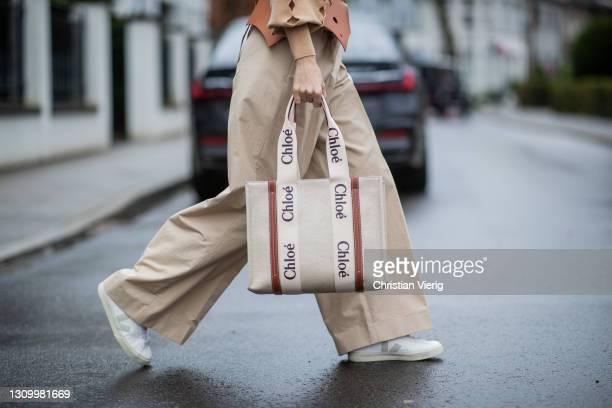 Alexandra Lapp is seen wearing LOEWE cut-out Obi belt in tan, CHLOÈ knitted jumper in beige, LOEWE pleated wide trousers in beige, CHLOÈ Woody...