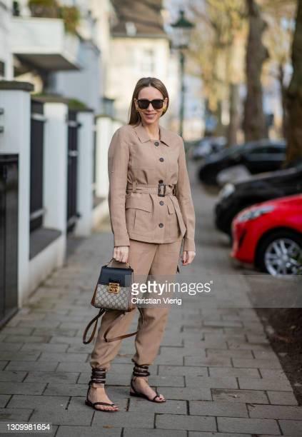 Alexandra Lapp is seen wearing MADELEINE blazer with belt and cargo pants in caramel, BOTTEGA VENETA Spiral Sandals in python print brown, GUCCI...
