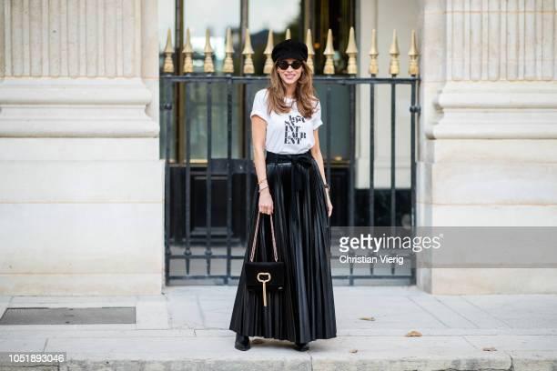 Alexandra Lapp is seen wearing pleated faux leather skirt in black by Nobi Talai white Saint Laurent 1971 TShirt black suede Baker Boy cap by Dior...