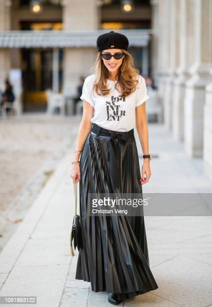 Alexandra Lapp is seen wearing pleated faux leather skirt in black by Nobi Talai white Saint Laurent 1971 TShirt black suede Baker Boy cap by Dior...