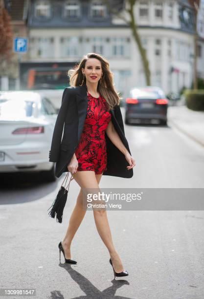 Alexandra Lapp is seen wearing SAINT LAURENT blazer in black, SAINT LAURENT jumpsuit in red and black, SAINT LAURENT Grace small hobo bag in black...