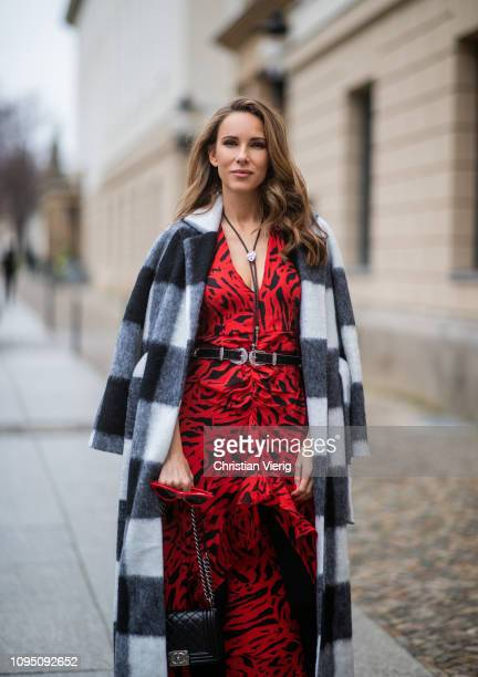 Alexandra Lapp is seen wearing the long Adriana animal print dress from Rixo a black and white wool coat from Ganni a black boy bag from Chanel a...