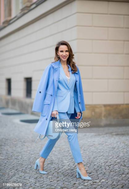 Alexandra Lapp is seen wearing total look Marc Cain: blue blazer, pants worn as a suit, round bag, wool coat, blue shoes during the Berlin Fashion...