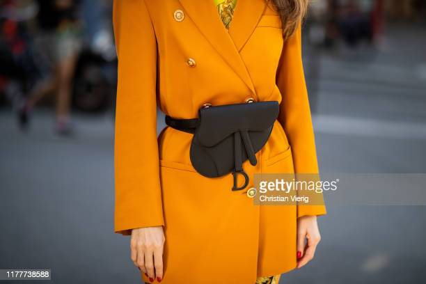 Alexandra Lapp is seen wearing Versage leggings and top in combination with Versace oversized blazer in cognac, black saddle belt clutch in...