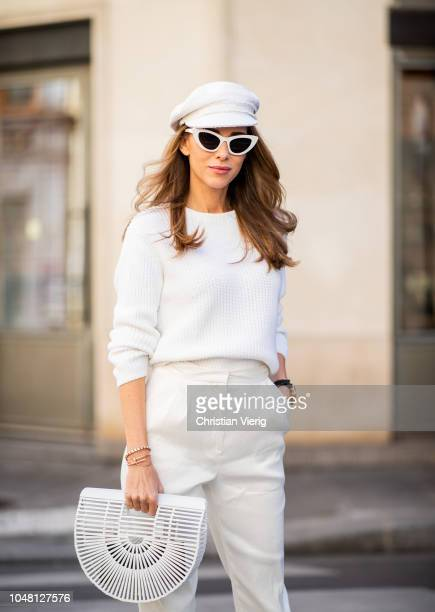 Alexandra Lapp is seen wearing white cropped trousers by Mansur Gavriel, a short knitted white pullover with a ring detail on the back from Ouì,...