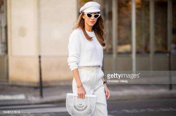 Alexandra Lapp is seen wearing white cropped trousers by Mansur Gavriel a short knitted white pullover with a ring detail on the back from Ouì white...
